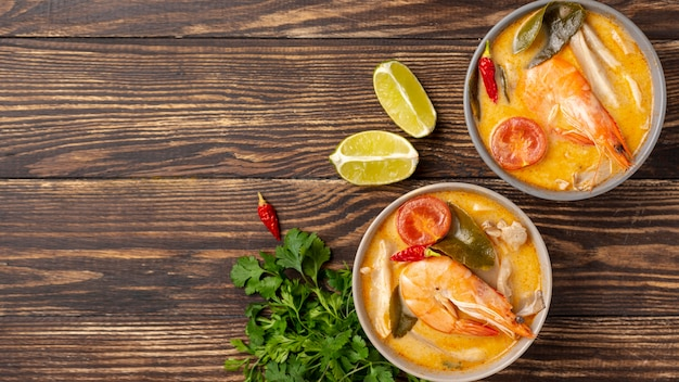 Flat lay soups in bowls with shrimp on wooden background with copy space Free Photo