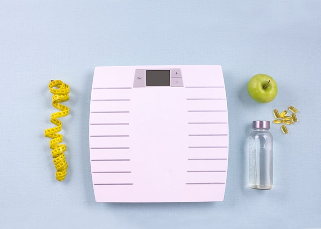 Flat Lay Sport Items Scales Water Apple Omega 3 On Blue Background Weight Loss Concept Top View Premium Photo