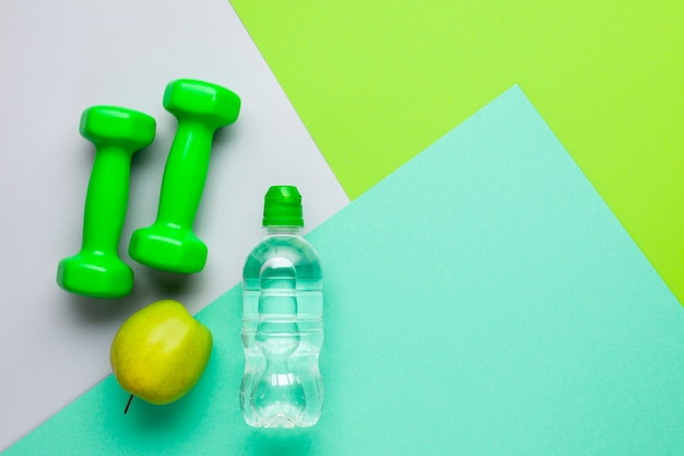 Flat lay sports attributes with water bottle and apple Free Photo