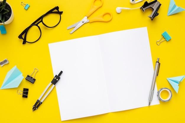 Disposizione piana della cancelleria di disposizione su fondo giallo con il taccuino vuoto Foto Gratuite