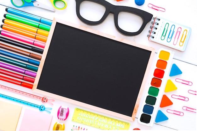 Плоско-канцелярские меловые доски, оправы для очков на белом столе Premium Фотографии