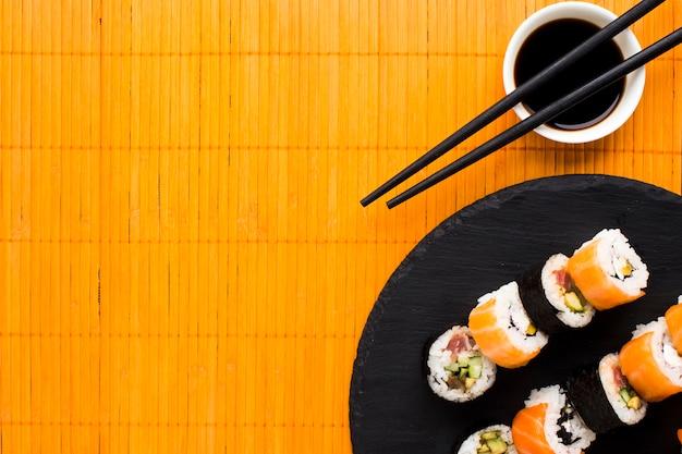 Flat lay sushi arrangement on orange bamboo mat Free Photo