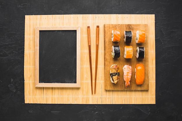 Flat lay sushi arrangement with black chalkboard Free Photo