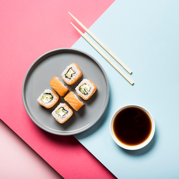 Flat lay sushi plate with chopsticks and soy sauce Free Photo