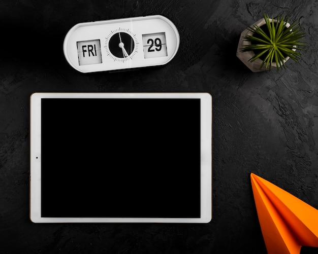 Flat lay of tablet clock and paper plane Free Photo