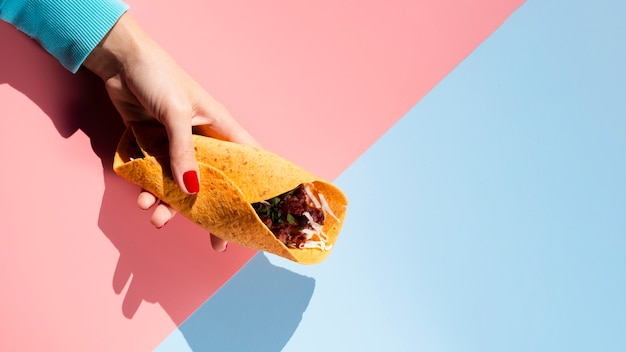 Flat lay taco with meat and veggies held in hand Free Photo