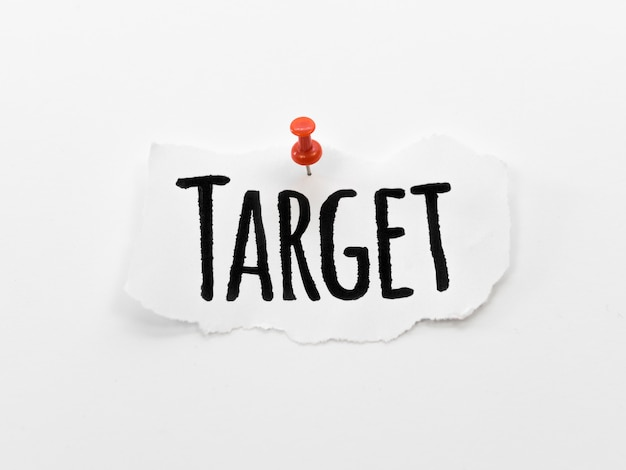 Flat lay of target written on piece of paper with pin Free Photo
