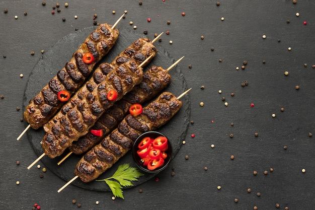 Lay piatto di gustosi kebab con condimenti sulla piastra Foto Gratuite