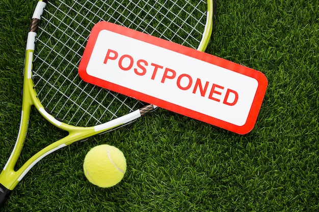 Flat lay tennis elements arrangement with postponed sign Free Photo