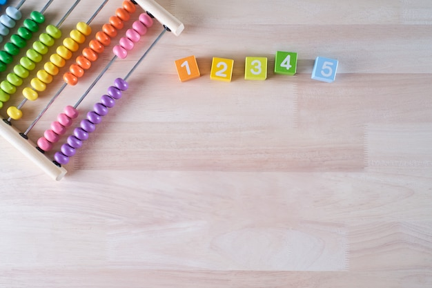 Flat lay, top view of bright colored wooden bricks and abacus toy background with copy space for text Premium Photo