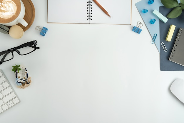 Flat lay, top view office workspace with blank note book, keyboard, office supplies. Premium Photo