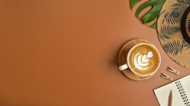 Flat lay, top view workspace with eye glasses, notebook, hat, pencil, green leaf, shoes and coffee cup on brown background. Premium Photo
