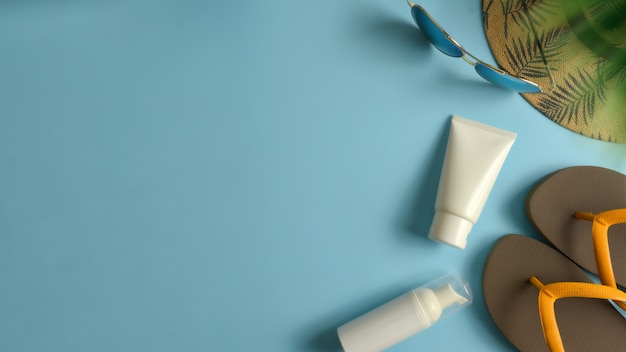 Flat lay, top view workspace with hat, sun block on blue background. summer stylish traveller blogger concept. Premium Photo