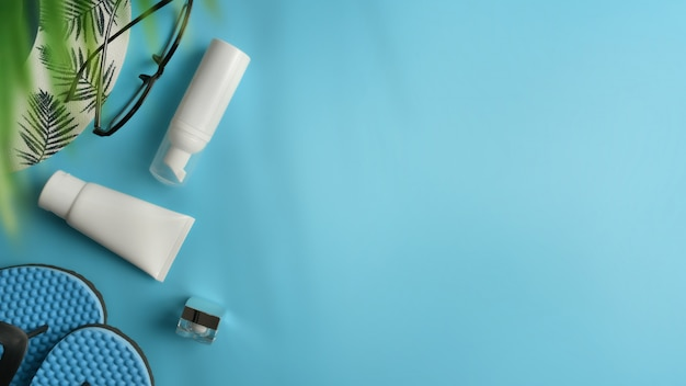 Flat lay, top view workspace with hat, sun block on blue background. Premium Photo