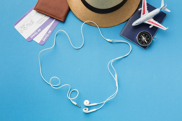 Flat lay of travel essentials with headphones and compass Free Photo