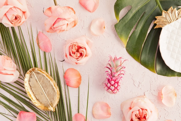 Flat lay of tropical workspace mockup with leaf plate, palm monstera leaves, pink flowers, pineapple and petals on pastel Premium Photo