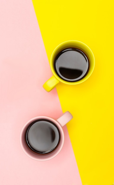 Flat lay of a two coffee cups with pink and yellow Premium Photo