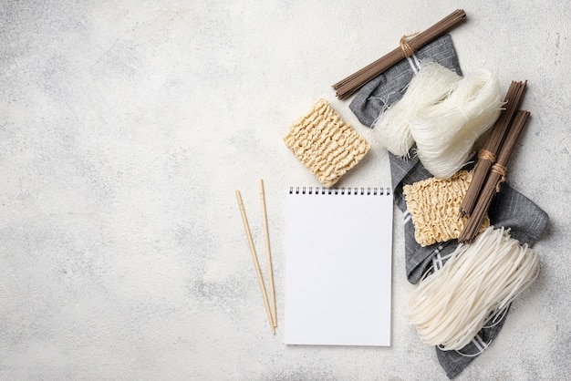 Flat lay uncooked assortment of noodles with blank notebook and copy space Free Photo