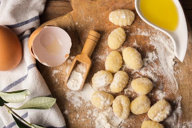 Gnocchi di patate crudi piatti distesi sul tagliere Foto Gratuite