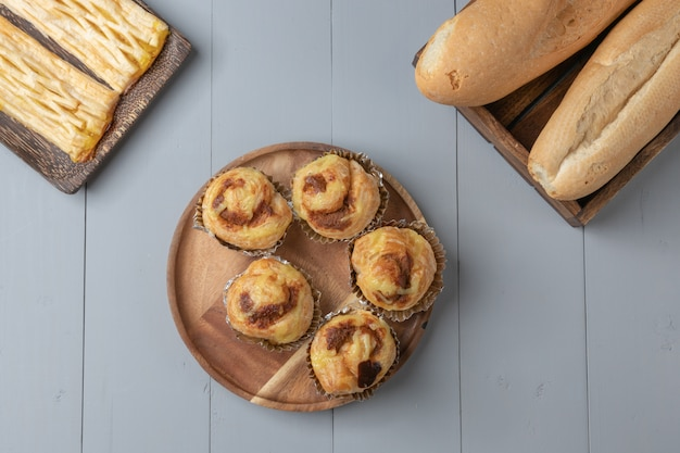 Flat lay of variety of bakery and danish shredded pork on wooden board Premium Photo