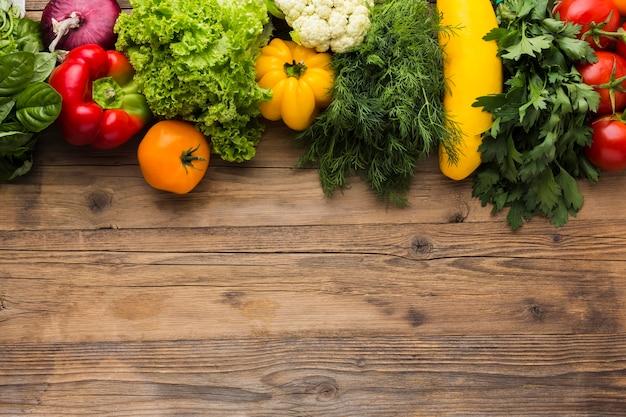 Плоский овощной ассортимент на деревянном фоне Premium Фотографии