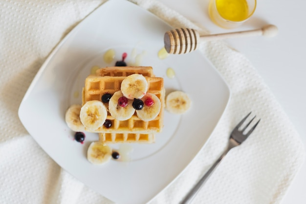 Flat lay of waffers with fruits and honey Free Photo