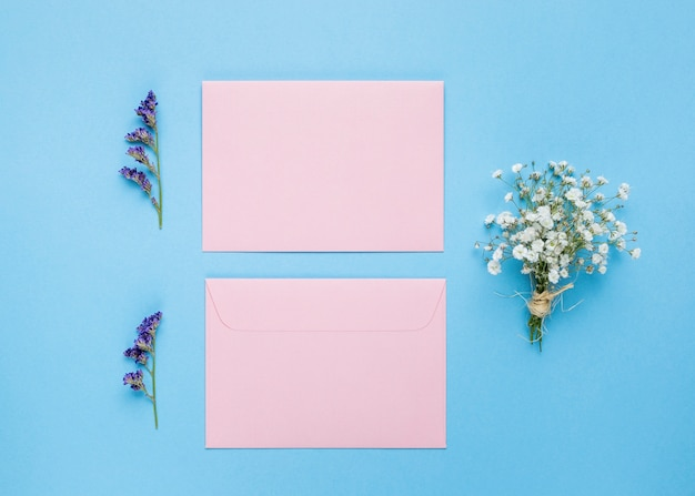 Flat lay wedding cards next to flowers Free Photo