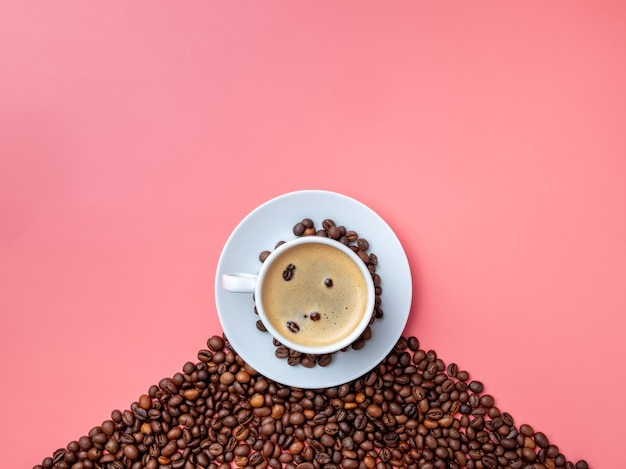 Плоская планировка. белая керамическая чашка с ароматным кофе на холме кофейных зерен на розовом фоне. Premium Фотографии