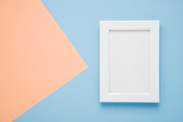 Flat lay white frame on light blue and pink background Free Photo