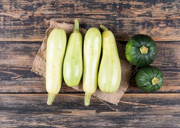 Zucchini bianchi e verdi piani di disposizione sulla tavola di legno scura Foto Gratuite