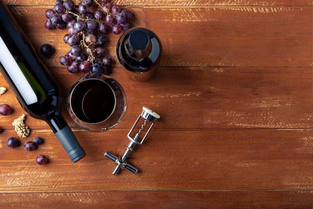 Flat lay wine bottle and glass with corkscrew Free Photo