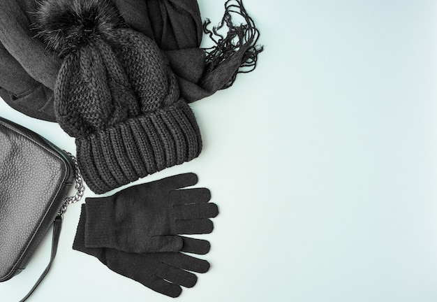 Flat lay winter or autumn warm woman accessories - black knitted scarf, hat, bag Premium Photo