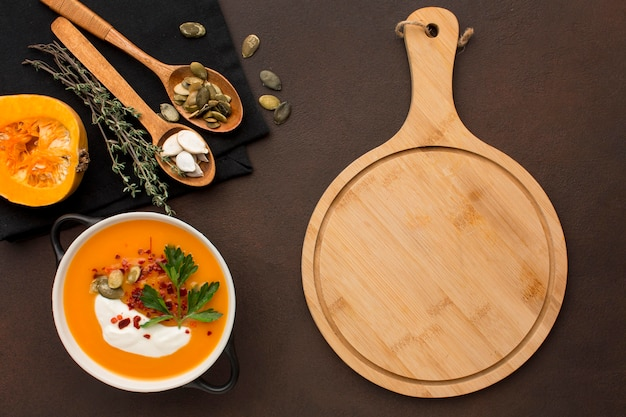 Flat lay of winter squash soup in bowl with chopping board and spoons Free Photo