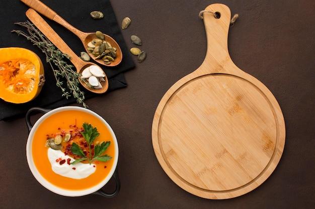 Lay piatto di zuppa di zucca invernale nella ciotola con tagliere e cucchiai Foto Gratuite