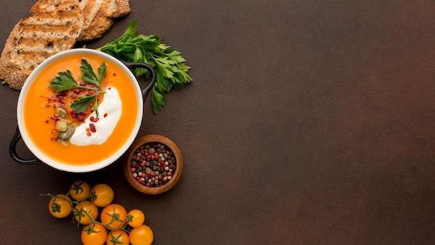 Lay piatto di zuppa di zucca invernale nella ciotola con toast e copia spazio Foto Gratuite