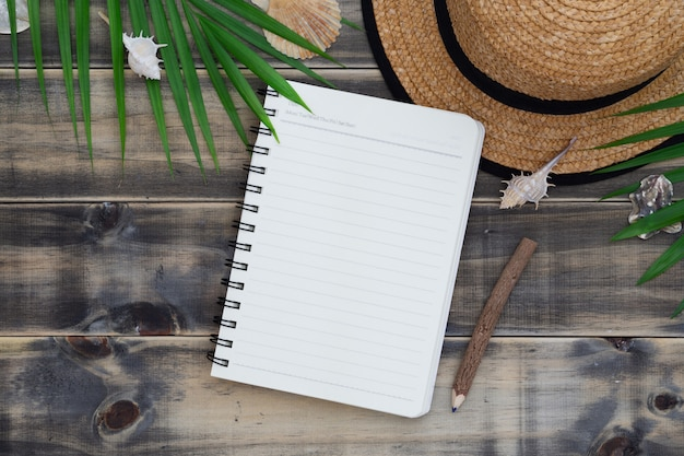 Flat lay with beach hat, sea shells, palm leaves and blank notebook and pencil. Premium Photo