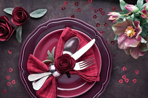 Flat lay with burgindy plates and crockery decorated with roses and anemones, christmas or valentine dinner setup Premium Photo