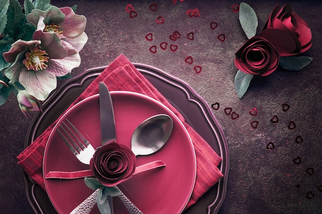 Flat lay with burgindy plates and crockery decorated with roses and anemones, Premium Photo