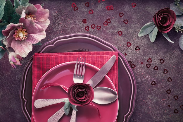 Flat lay with burgindy plates and crockery decorated with roses and anemones Premium Photo