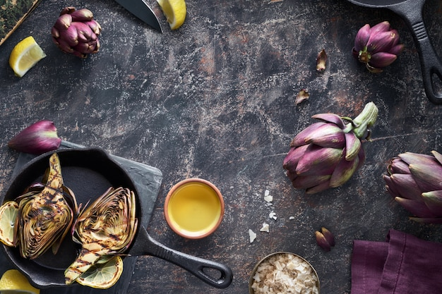 Flat lay with fresh and grilled red artishokes on dark textured background with copy-space Premium Photo