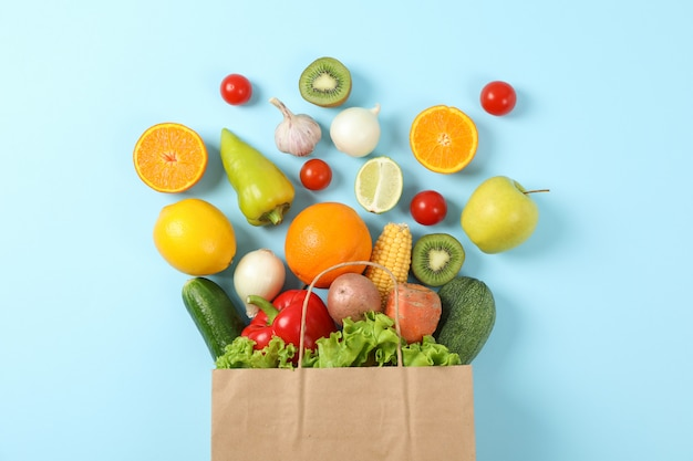 Premium Photo | Flat lay with paper bag, vegetables and fruits on blue
