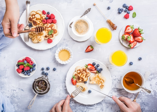 Flat lay with scotch pancakes in flower form, berries and honey with human hands Premium Photo