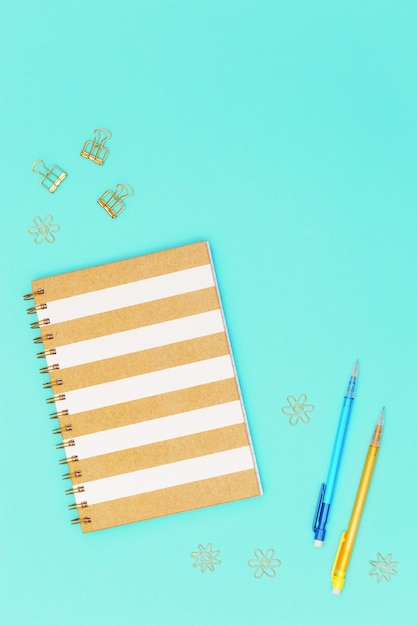 Flat lay with stationery for school, education. closed notebook on spring, pencil, golden metal clips for paper. Premium Photo
