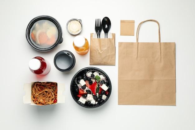 フラットは白い壁に持ち帰り用の食品を置きます。食品配達 Premium写真