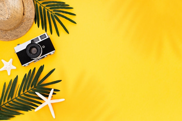 Flat lay with traveler accessories: tropical palm leaf, retro camera, sun hat,  starfish on yellow background Free Photo