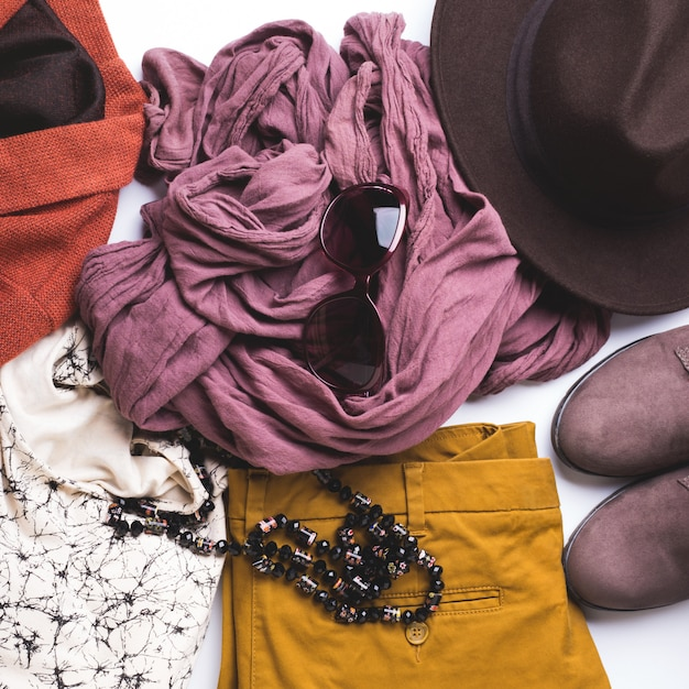 Flat lay with woman's autumn clothes, glasses hat Premium Photo