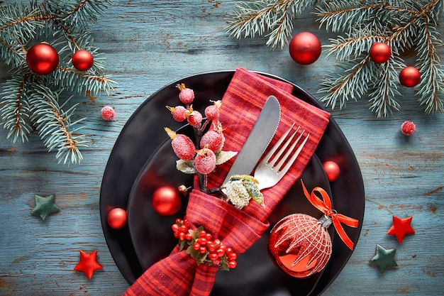 Flat lay with xmas decorations in green and red with frosted berries, trinkets, plates and crockery Premium Photo