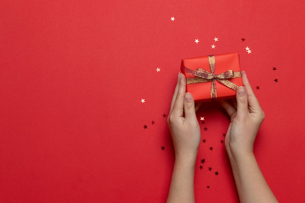 Flat lay of woman hands holding surprise gift box wrapped and decorated with bow with gold stars on red background. birthday, valentines day, christmas, new year. flat lay style Premium Photo