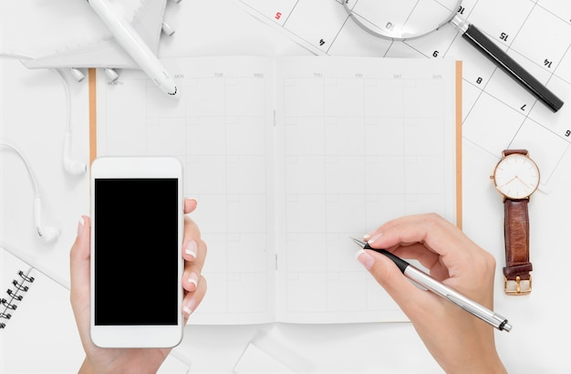 Flat lay of woman hands using smartphone and writing on travel itinerary plan with blank space Premium Photo