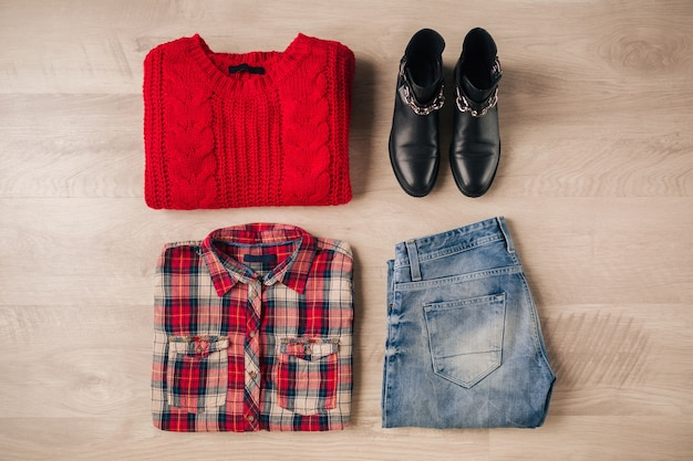 Flat lay of woman style and accessories, red knitted sweater, checkered shirt, denim jeans, black leather boots, autumn fashion trend, view from above, clothes Free Photo